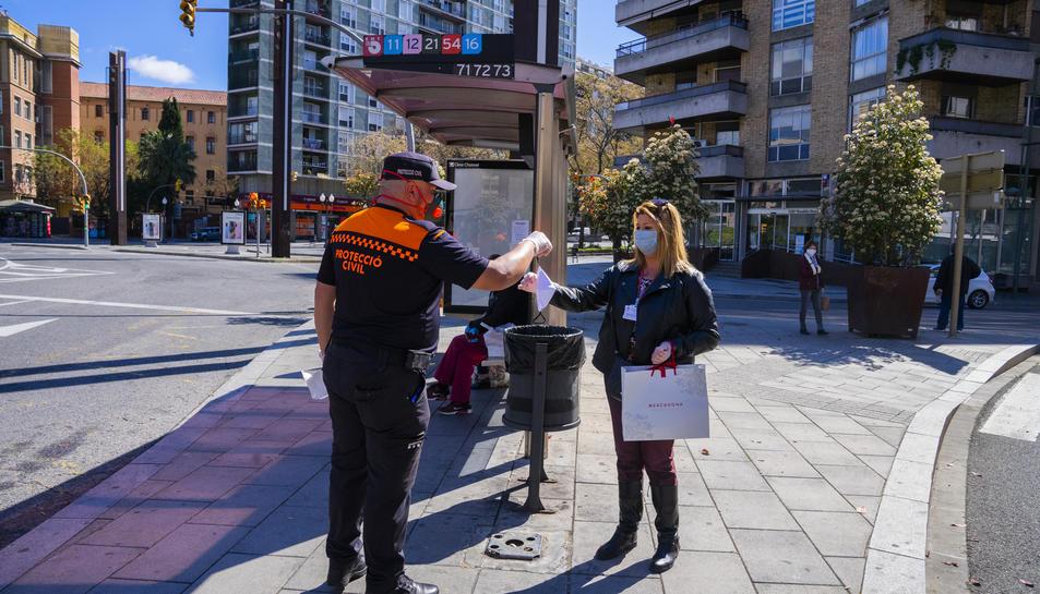 Un voluntari de Protecció Civil entregant una mascareta a una usuària de l'EMT a la parada de la plaça Imperial Tàrraco.
