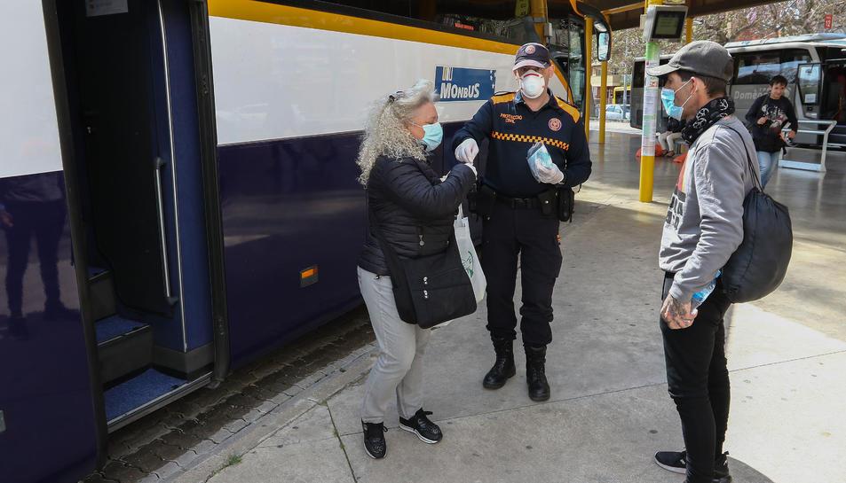 Un voluntari donant una mascareta a l'estació de busos de Reus.