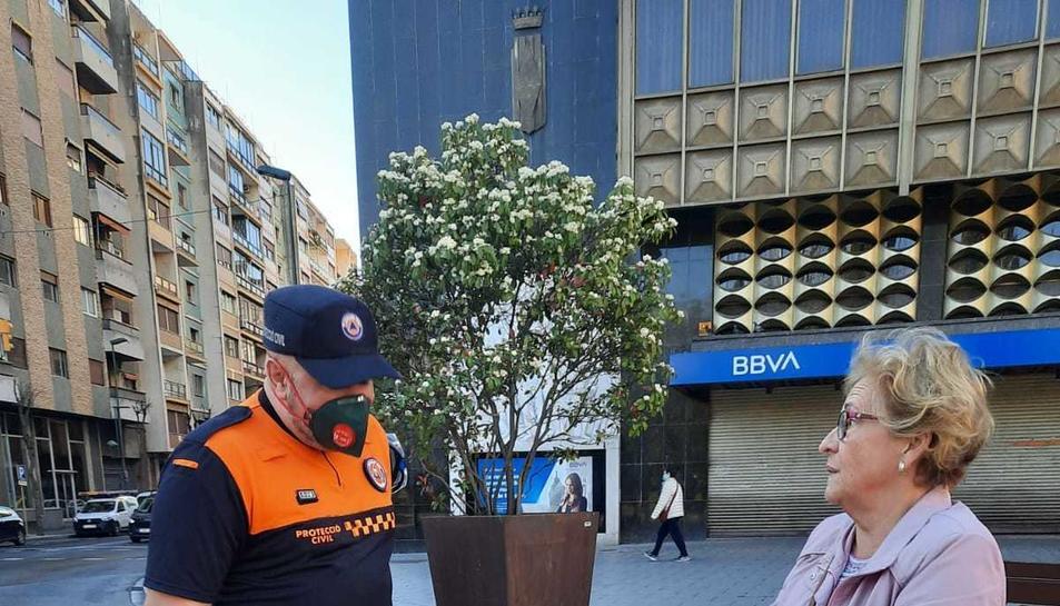 Un membre de Protecció Civil donant una mascareta a una dona a l'autobusos de Tarragona.