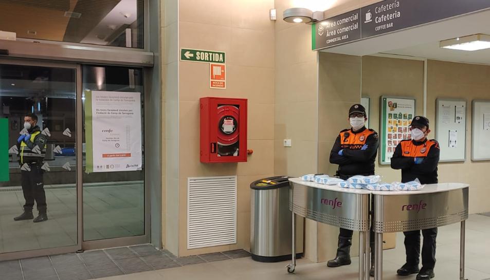 Dos membres de Protecció Civil a punt per repartir mascaretes a l'estació de tren de Tarragona