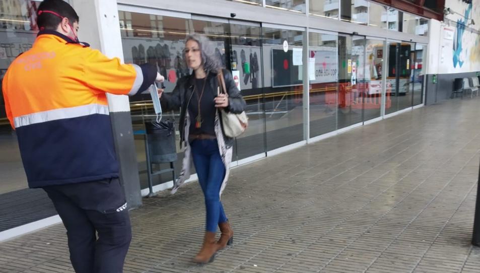 Un membre de Protecció Civil donant una mascareta a una usuària a l'estació d'autobusos de Tarragona.