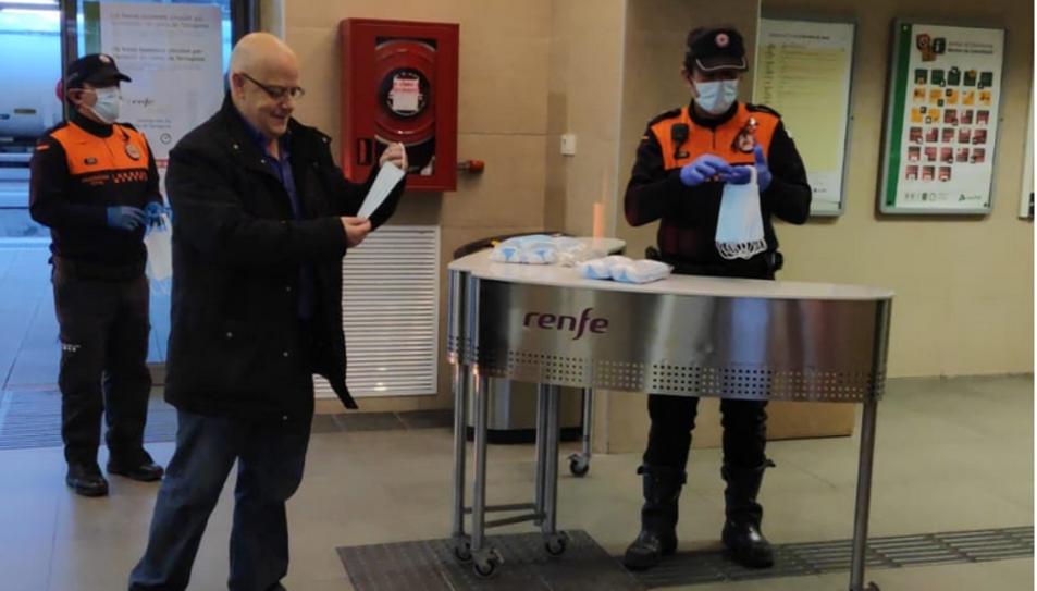 Un usuari de tren posant-se la mascareta que li han entregat.