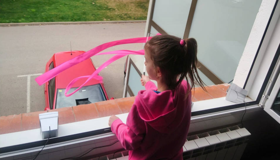 Una nena a la finestra de casa seva a Ripoll.