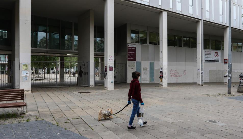 Una persona passeja un gos davant de l'accés a l'interior del Campus Catalunya tancat.