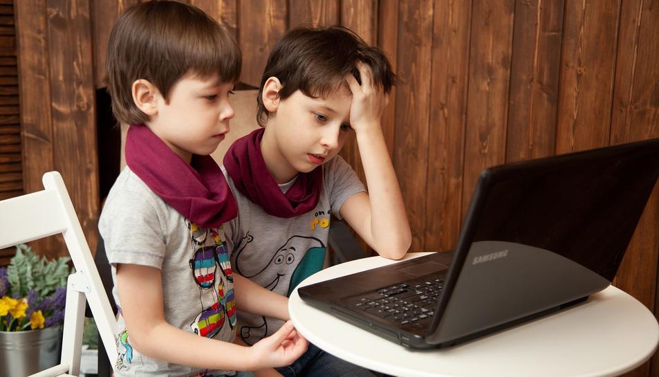 Dos nens davant un ordinador portàtil.