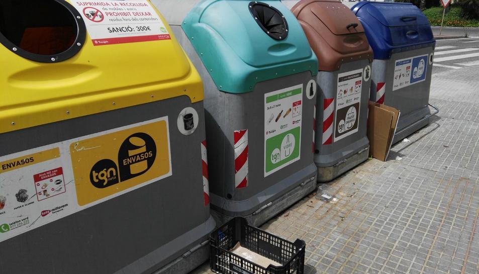 Una capsa als peus d'un contenidor amb un cartell que diu que està prohibit deixar voluminosos.