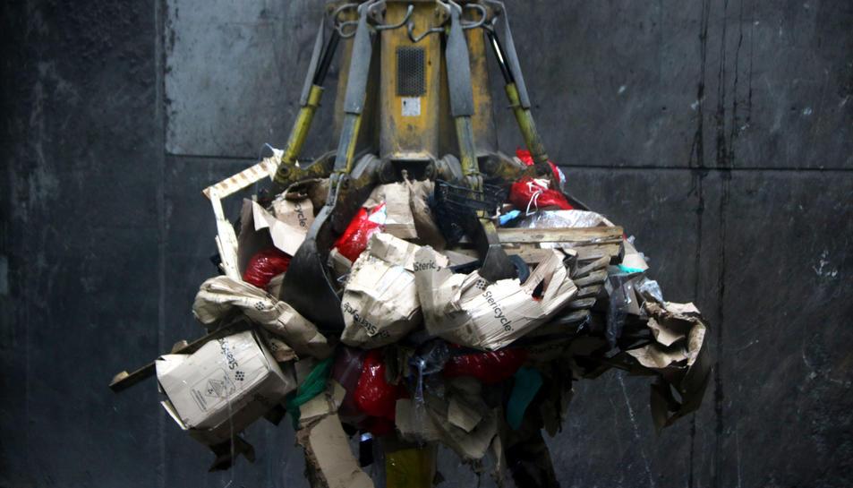 El ganxo d'una grua elevant diverses bosses de residus sanitaris per introduir-les al forn de la incineradora Sirusa de Tarragona.