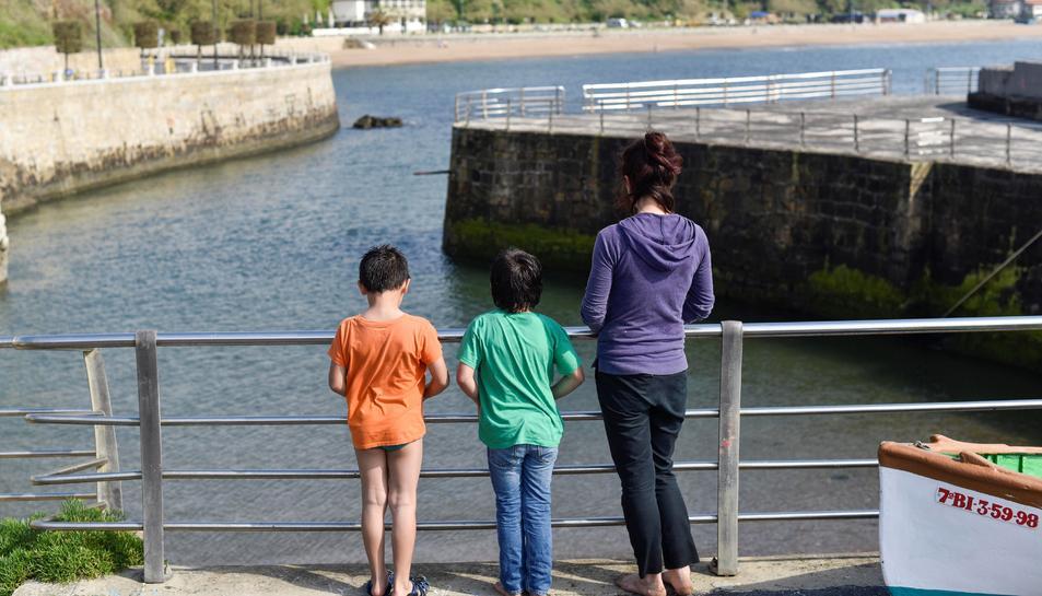 Una dona passeja amb els seus fills pel Port Vell de Getxo (Bizkaia), aquest diumenge en el qual es compleixen 43 dies de confinament i en el qual més de sis milions de nens menors de 14 anys poden sortir al carrer una hora al dia, al costat d'un adult i a un quilòmetre com a màxim de les seves cases.