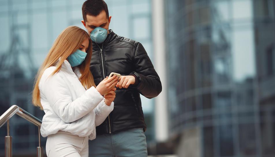 Imatge d'una parella amb mascareta al carrer durant el decret d'alarma pel coronavirus.