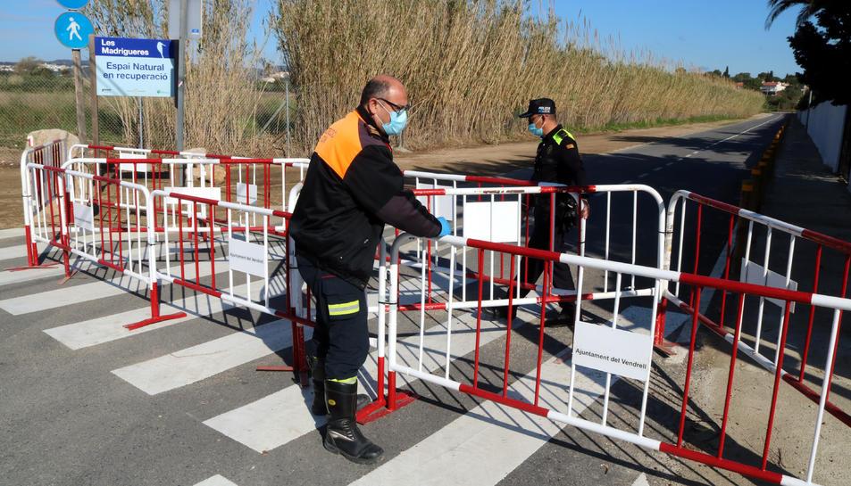 Efectius de Protecció Civil i de la Policia Local del Vendrell acabant de col·locar les tanques en un accés secundari, a l'entorn de les Madrigueres.