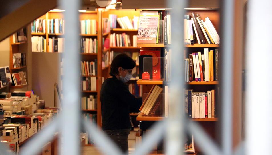 Una llibreria amb la persiana abaixada, però amb els seus empleats treballant per Sant Jordi.