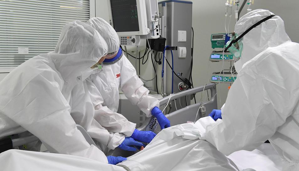Pla mig dels sanitaris amb un pacient a la UCI de l'Hospital de Manresa.