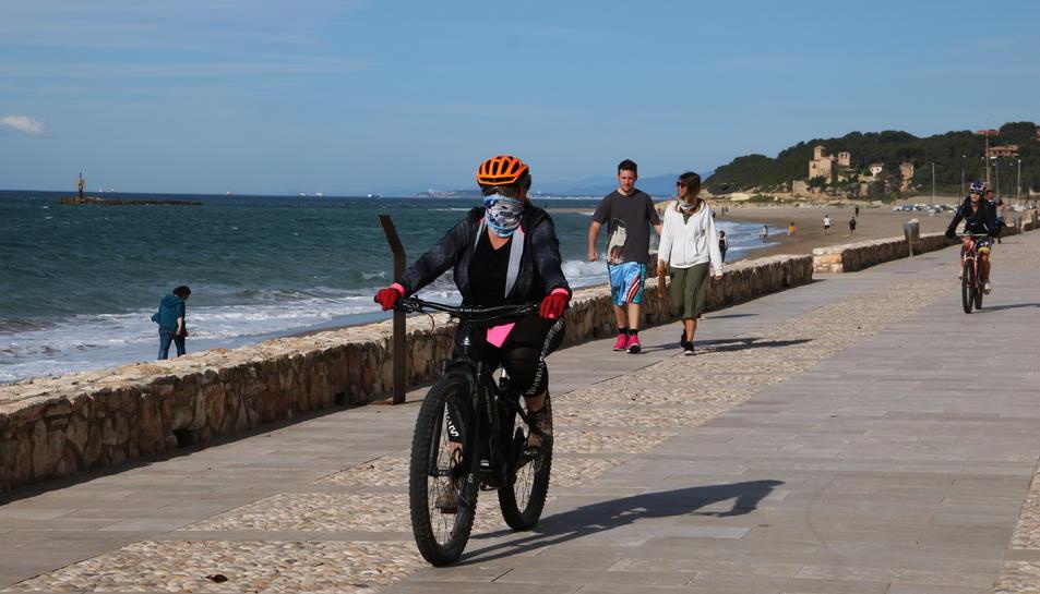 Cciclistes i persones caminant al passeig marítim d'Altafulla en el primer dia permès per sortir a passejar i practicar esport
