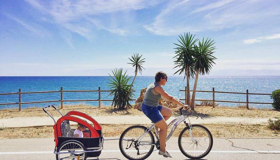 Pla general d'una dona amb bicicleta passejant un infant al municipi d'Alcanar