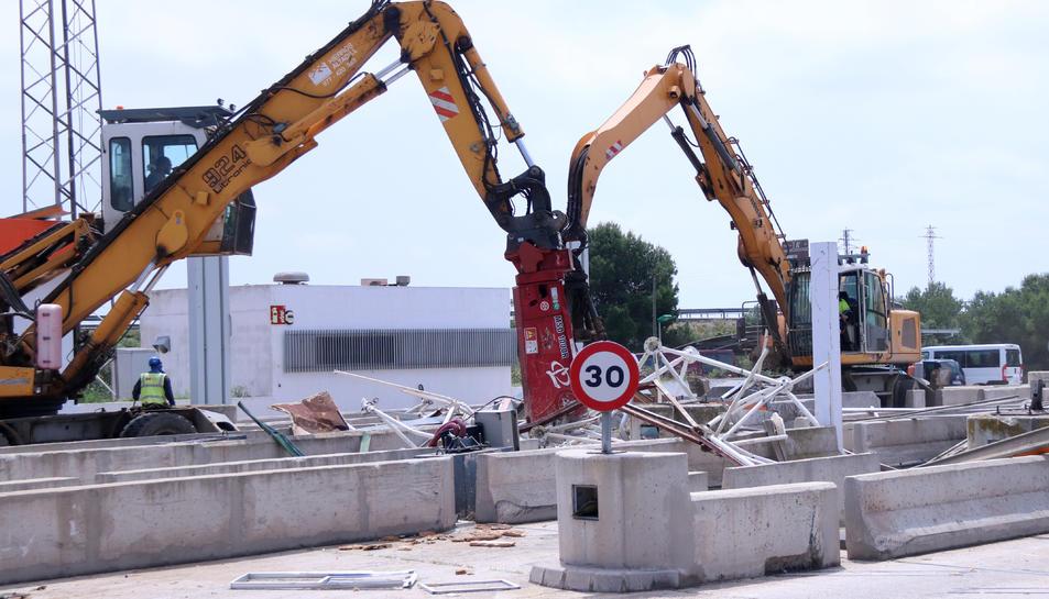 Dues màquines treballant en la retirada de les estructures del peatge de l'Aldea de l'AP-7.