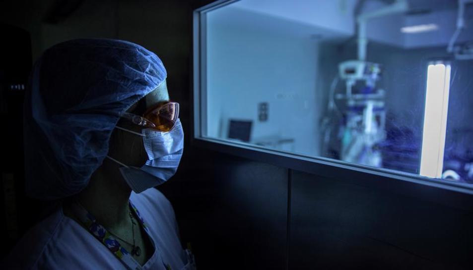 Una sanitària observa el funcionament d'un dispositiu de llum ultraviolada continua (UV-C) mòbil que serveix per desinfectar les estances hospitalàries i eliminar el coronavirus.