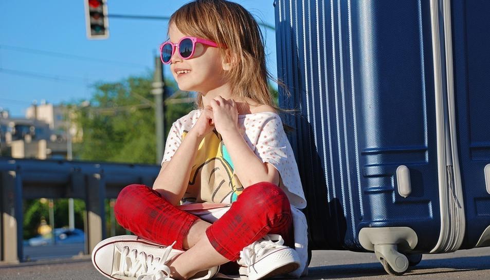 Imatge d'una nena amb ulleres de sol al carrer.