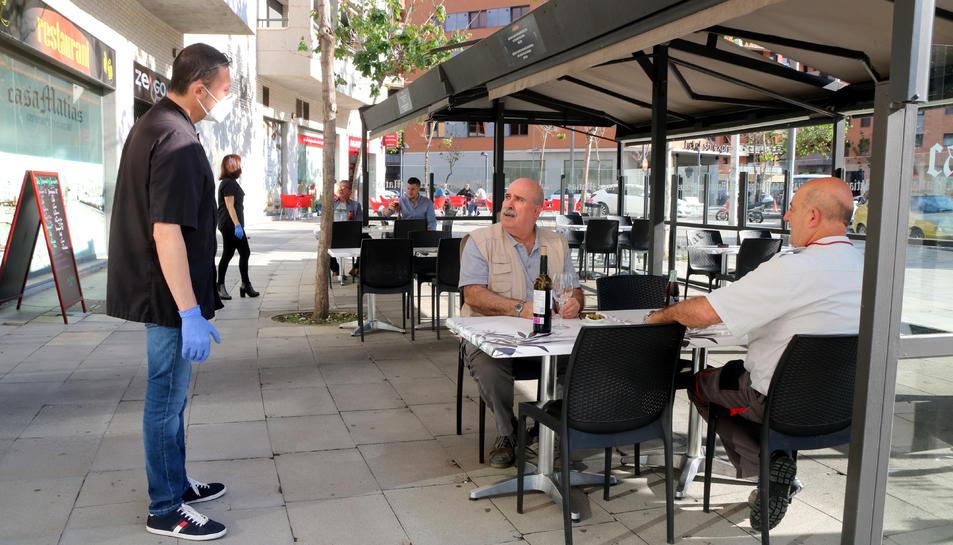 El propietari del bar restaurant Casa Matías de Tarragona enraonant amb els primers clients que té a la terrasa amb motiu del pas a la fase 1.