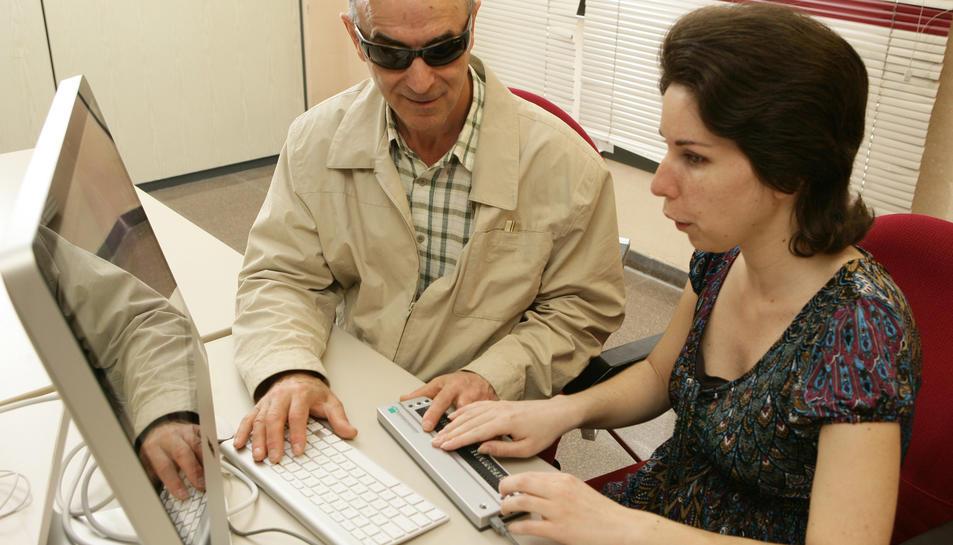 Dues persones cegues treballant amb l'ordinador.