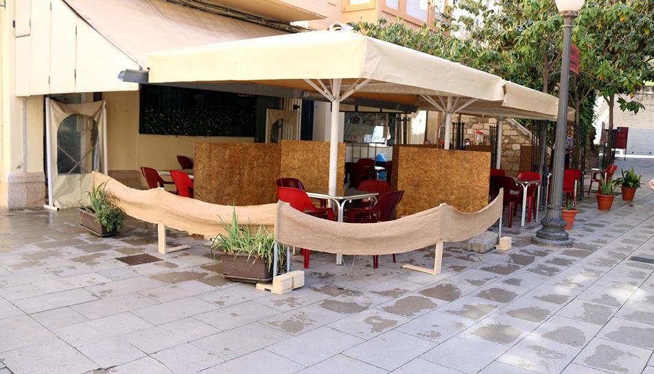 La terrassa d'un bar del centre de Tortosa amb mampares de fusta que separen les taules