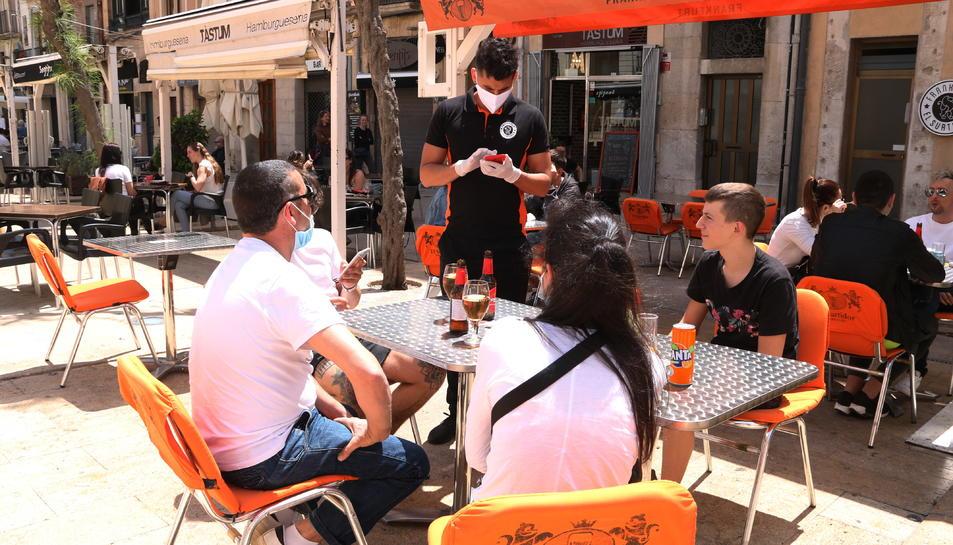 Pla obert d'un cambrer anotant la comada a uns clients en una terrassa de la plaça de la Font de Tarragona en el primer dissabte de la fase 1.