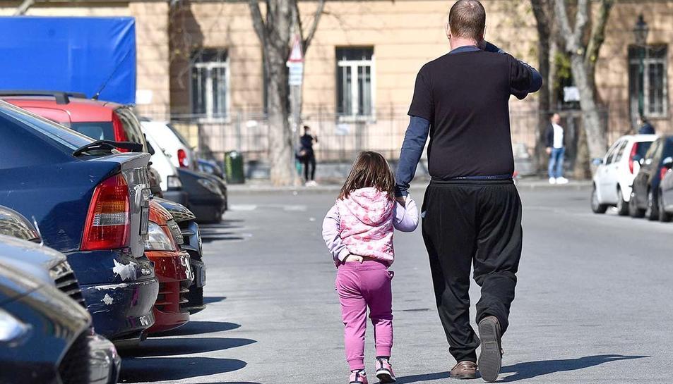 Un pare acompanya la seva filla pel carrer.