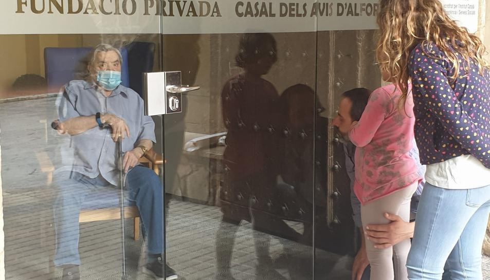 Moment del retrobament entre Nicolás Méndez amb el seu fill i les seves nétes, a les quals només ha pogut veure a través de la porta.