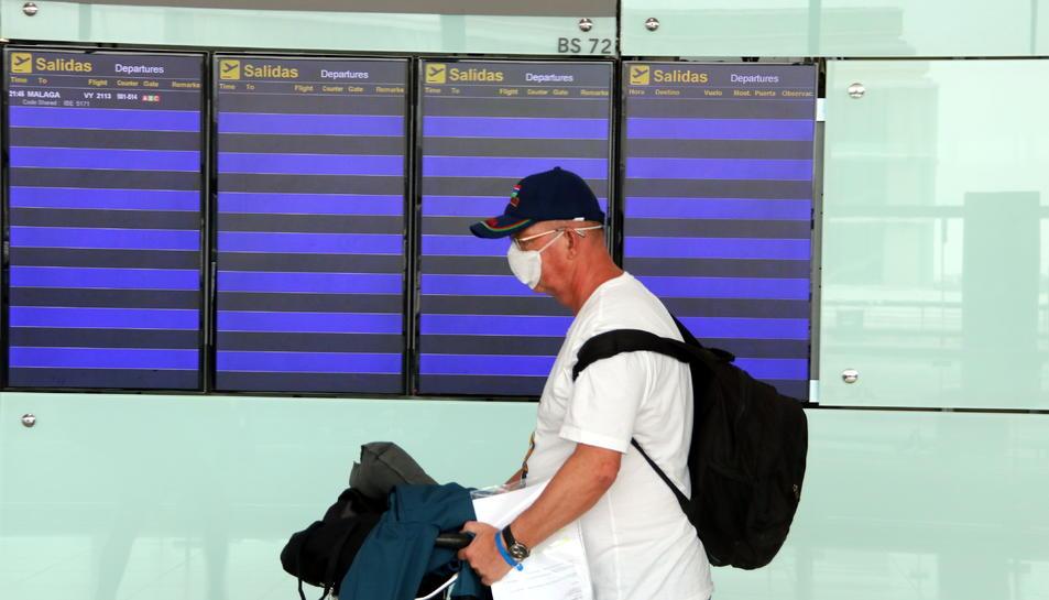 Imatge d'un viatger amb mascareta passant per davant dels panells informatius sense cap vol el 18 de març de 2020.
