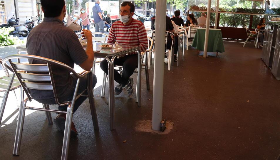 Pla obert d'un grup de persones assegudes a la terrassa d'un bar a la la Rambla de Catalunya en el primer dia de fase 1 a Barcelona.