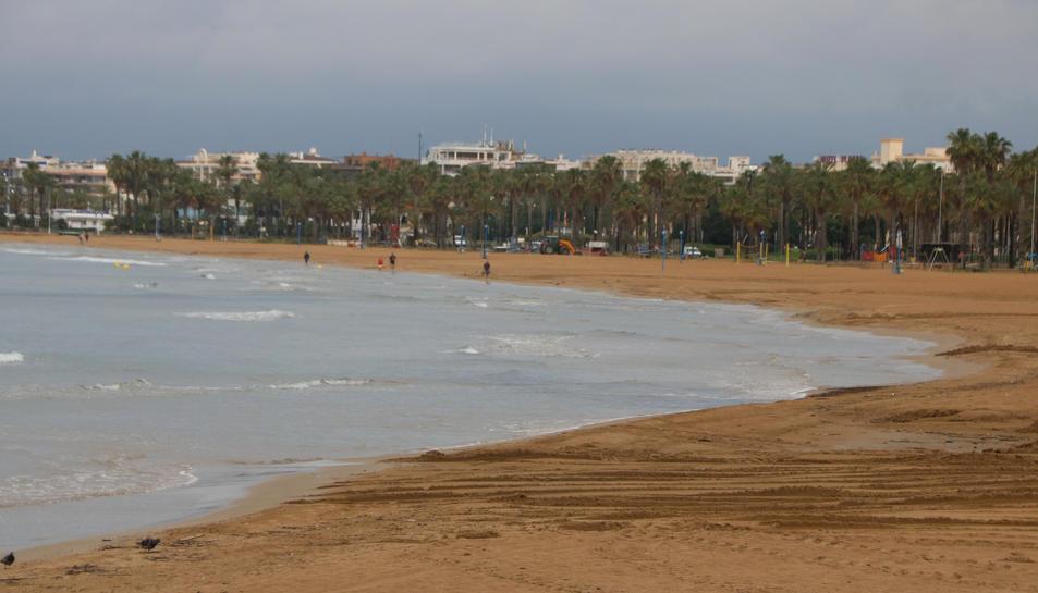 La platja de Llevant de Salou amb només algunes persones passejant vora el mar.