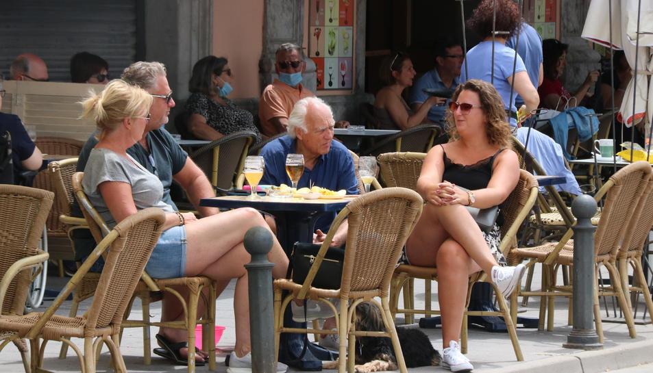 Un grup de persones prenen una cervesa en una terrassa