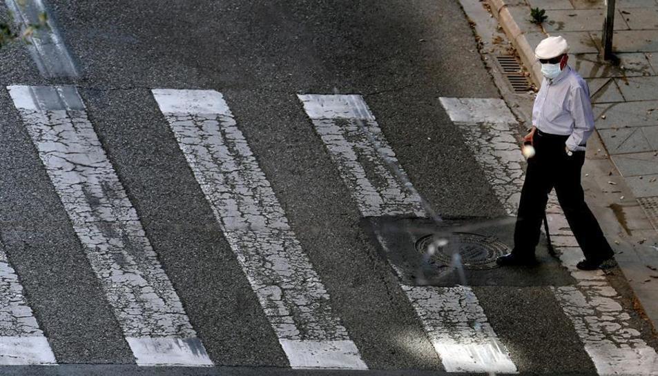 Una persona gran passejant pel carrer.