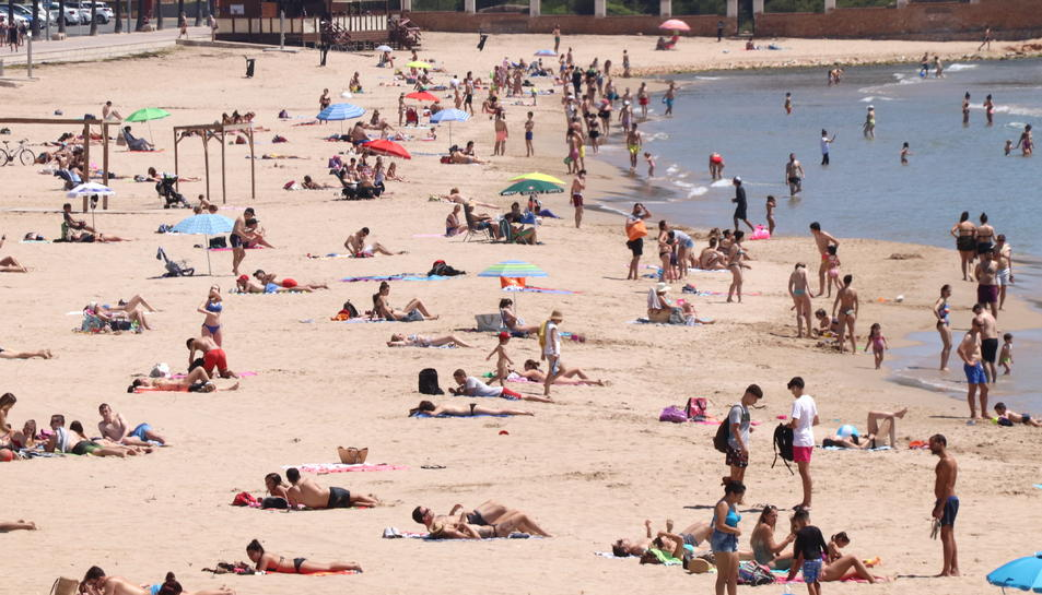 La platja de l'Arrabassada de Tarragona, amb banyistes i gent prenent el sol.