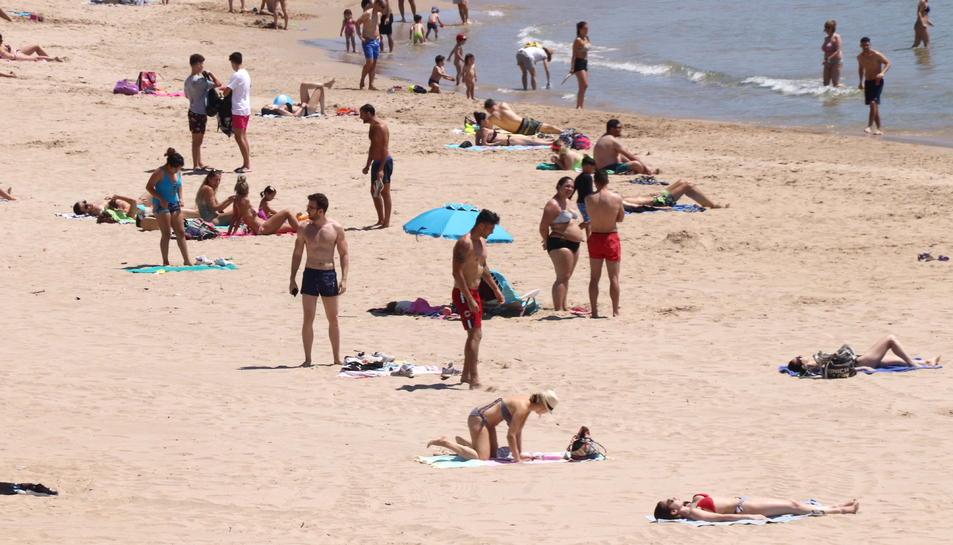 Persones prenent el sol a la platja de l'Arrabassada de Tarragona.