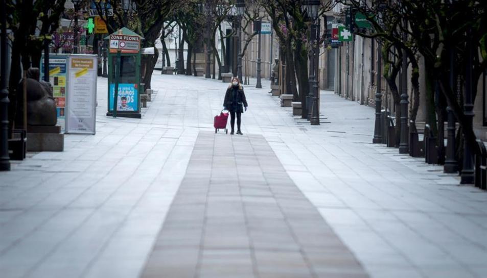 Una dona passejant pel carrer.