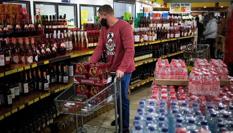 Un home comprant alcohol en un supermercat.
