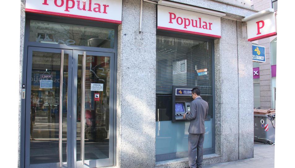 Imatge d'arxiu d'un home treient diners al banc popular.