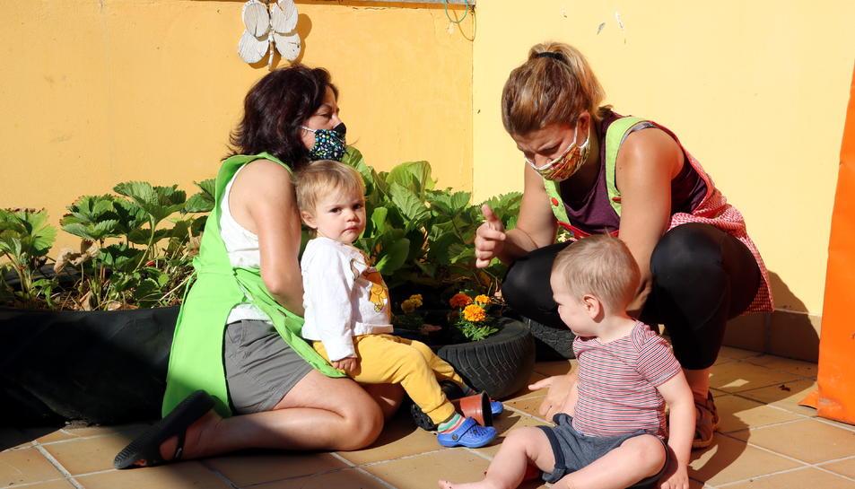 Dues professores amb mascareta amb dos infants a la llar d'infants del Pallars Sobirà.
