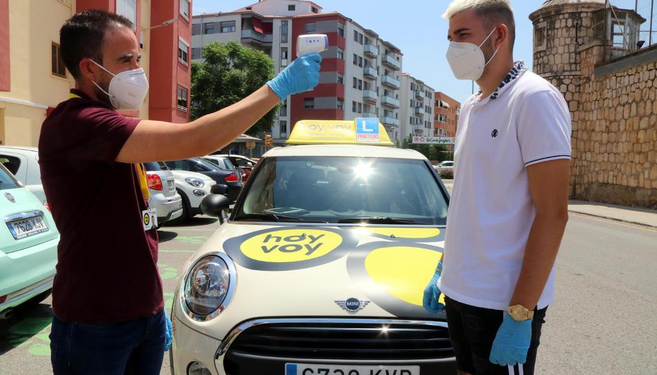 Un professor de l'autoescola Hoy-voy Tarragona prenent la temperatura a un alumne abans de començar una classe pràctica de cotxe.
