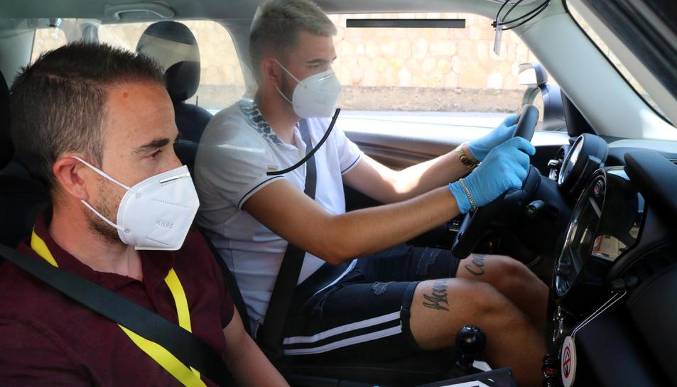 Un professor de l'autoescola Hoy-voy Tarragona i un alumne, amb guants i mascareta durant una classe pràctica de cotxe.
