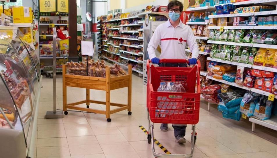 Un voluntari de la Creu Roja fa la compra en un supermercat.
