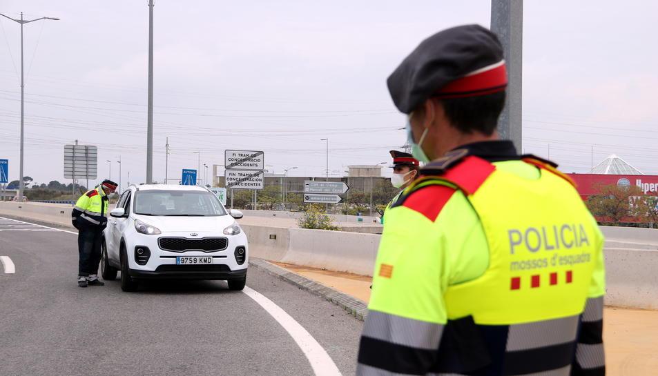 Un agent dels Mossos d'Esquadra en primer terme i un vehicle al control policial de la T-11 a Tarragona.