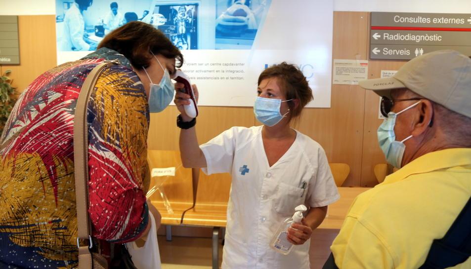 Una infermera prenent la temperatura a dos pacients abans que entrin a consultes externes de l'Hospital Verge de la Cinta de Tortosa.