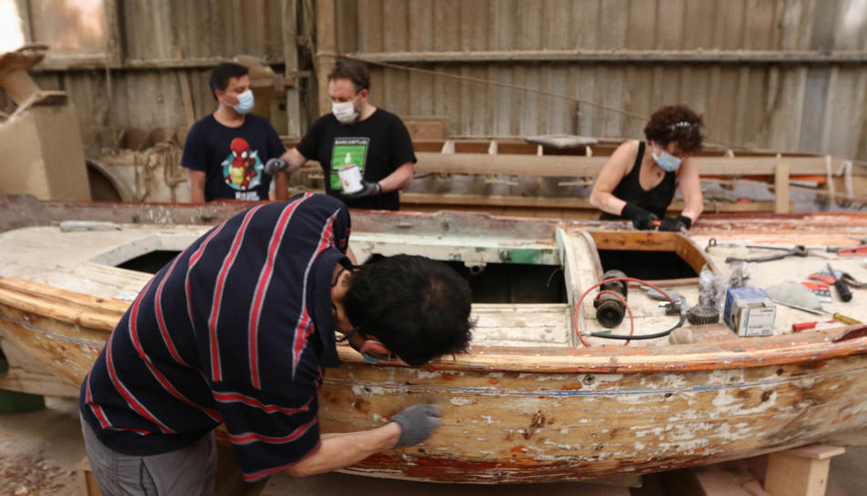 Els membres de La Toneta treballant en la barca.