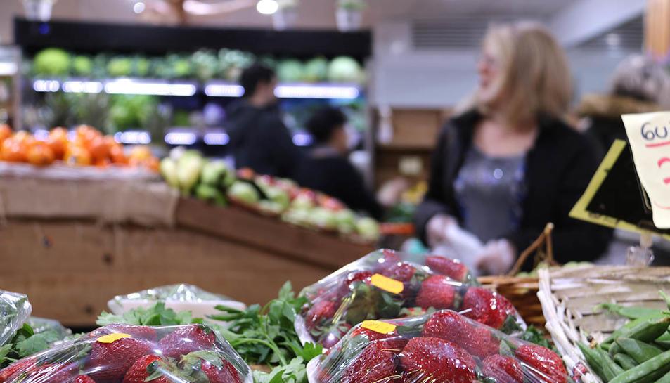 Diversos clients en una fruiteria de mercat.