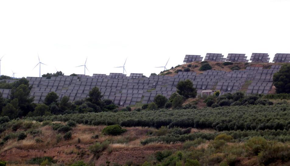 Algunes plaques solars del parc de Flix amb alguna aerogeneradors d'un parc eòlic al fons.