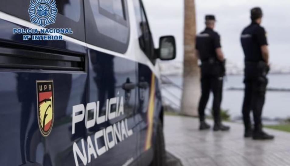 Agents de la Policia Nacional al costat d'un cotxe patrulla.