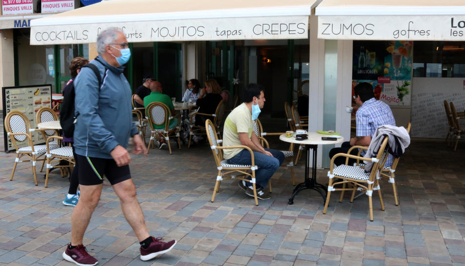 Pla general de la terrassa d'una cafeteria a Calafell Platja mentre un home passeja amb mascareta.
