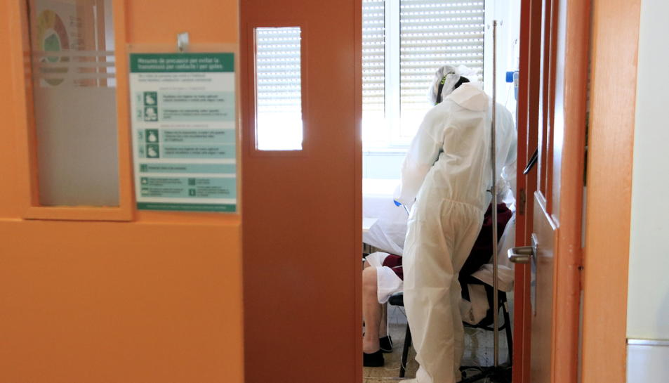 Una professional sanitària al costat d'un pacient amb covid-19 que parla amb la seva família a través d'una tauleta a l'Hospital del Mar.