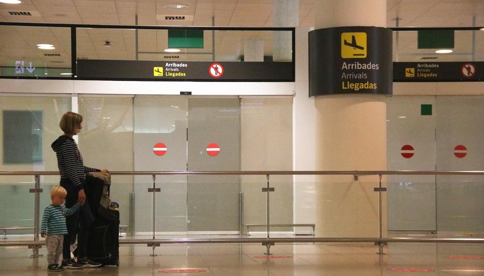 Pla general d'una passatgera esperant davant la zona d'arribades a l'aeroport de Barcelona.